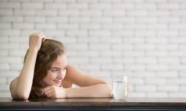 Junge Frau in den frohen Lagen mit Krug und Glas Trinkwasser lizenzfreies stockbild