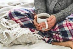 Junge Frau in den gemütlichen Pyjamas und grauen in der Wolljacke, die auf einem Bett mit einem Becher Tee sitzt Stockbilder