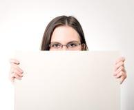 Junge Frau in den Gläsern, die eine weiße Karte anhalten stockfotografie
