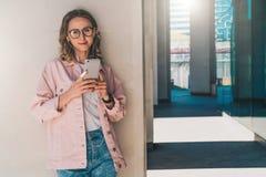 Junge Frau in den Gläsern steht nahe weiße Wand im Freien und hört Musik auf ihrem Smartphone Lizenzfreie Stockfotografie