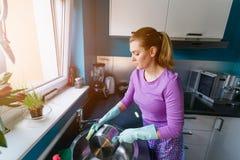 Junge Frau in den Gummihandschuhen, die Teller waschen stockfoto