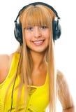 Junge Frau in den Haupttelefonen Stockfotos