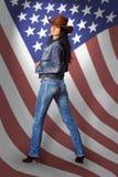 Junge Frau in den Jeans mit amerikanischer Flagge stockfotos