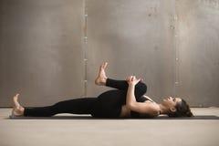 Junge Frau in den Knien zum Kasten, Apanasana-Haltung, graues Studio lizenzfreie stockbilder