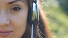 Junge Frau in den Kopfhörern hört Musik Porträtnahaufnahme stock footage