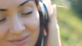 Junge Frau in den Kopfhörern hört Musik Porträtnahaufnahme stock video footage