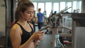 Junge Frau in den Kopfhörern mit dem Telefon, das zuhause in der Turnhalle steht stock video