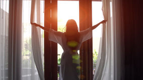 Junge Frau in den offenen Vorhängen des Bademantels und Ausdehnung, die zu Hause nahe dem Fenster steht lizenzfreies stockbild