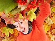Junge Frau in den orange Blättern des Herbstes. Stockfotografie