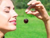 Junge Frau in den Perlen gemacht von der frischen Kirsche, die Kirsche auf offenem Mund mit Sommergrün-Waldhintergrund hält Stockfotografie