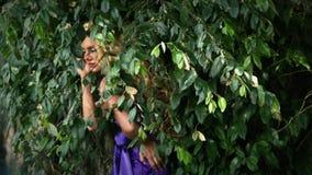 Junge Frau in den purpurroten Kleiderhaltungen stock footage