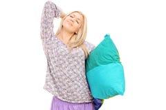 Junge Frau in den Pyjamas, die Kissen halten und sich ausdehnen Lizenzfreie Stockfotos