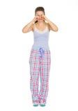 Junge Frau in den Pyjamas, die Augen reiben Stockbild
