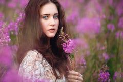 Junge Frau in den rosafarbenen Blumen Stockfoto