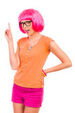 Junge Frau in den schwarzen Gläsern und in der rosa Perücke oben zeigend. Lizenzfreies Stockfoto