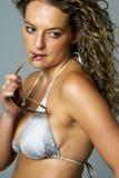 Junge Frau in den silbernen Bikiniholding-Sonnegläsern Stockfotos