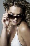 Junge Frau in den silbernen Bikiniholding-Sonnegläsern Stockfotografie