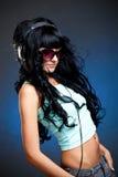 Junge Frau in den Sonnenbrillen mit Kopfhörern Stockfotografie