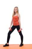 Junge Frau in den Sportkleidungstrainingsbeinen und -händen mit den Dummköpfen stockbilder