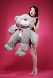 Junge Frau in den Strümpfen erotisch, ihr weiches Lieblingsspielzeug streichend lizenzfreie stockfotos