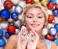Junge Frau in den Weihnachtskugeln. Lizenzfreies Stockfoto