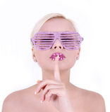 Junge Frau in den Zauberrosagläsern mit dem Finger auf ihren Lippen lizenzfreie stockfotografie