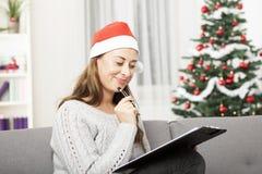 Junge Frau denken an Weihnachten mit Liste Lizenzfreie Stockfotografie
