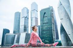 Junge Frau in der Affe-Gotthaltung gegen den Wolkenkratzer Lizenzfreies Stockfoto