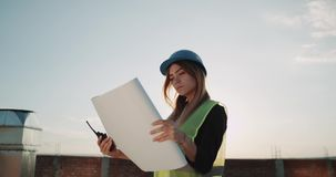 Junge Frau an der Baustelle die Karte des Baus analysierend stock footage