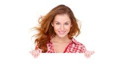 Junge Frau in der beiläufigen Kleidung, die leeren Vorstand anhält Stockfoto