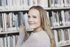 Junge Frau in der Bibliothek Lizenzfreie Stockfotos