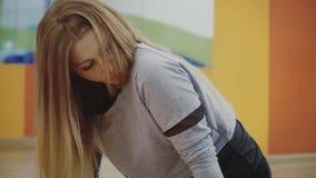 Junge Frau der Blondine recht, welche die ausdehnende Übung in der Turnhalle tut stock video footage