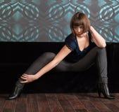 Junge Frau in der dunklen Kleidung, die auf Sofa sitzt lizenzfreie stockfotos