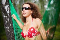 Junge Frau in der dunklen Sonnenbrille und im roten Badeanzug sitzt in der Hängematte Stockbild