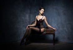 Junge Frau in der dunklen Wäsche Stockfotografie