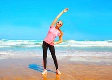 Junge Frau der Eignung, die Übung auf dem Strand ausdehnend tut Lizenzfreie Stockbilder
