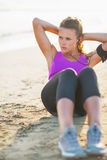 Junge Frau der Eignung, die Abdominal- Krise auf Strand tut Stockfoto