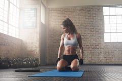 Junge Frau der Eignung, die auf Yogamatte an der Turnhalle sitzt Lizenzfreies Stockfoto