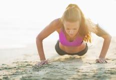 Junge Frau der Eignung, die das Handeln drückt, ups auf Strand Stockfoto