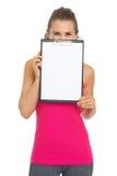 Junge Frau der Eignung, die hinter leerem Klemmbrett sich versteckt Lizenzfreies Stockbild