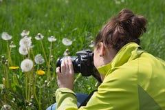 Junge Frau in der Freizeit, die Naturfotos im Gras macht Lizenzfreies Stockbild