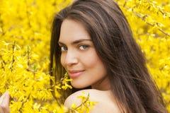 Junge Frau in der geblühten, gelben Zeit des Gartens im Frühjahr lizenzfreie stockfotos