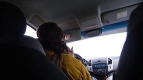 Junge Frau in der gelben Jacke, die im Auto sitzt und auf dem Spiegel schaut lizenzfreie stockfotografie