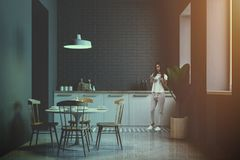 Junge Frau in der grauen Ziegelsteinküche und in Esszimmer Lizenzfreies Stockfoto