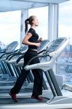 Junge Frau an der Gymnastik. Laufen Sie auf eine Maschine Stockfotos