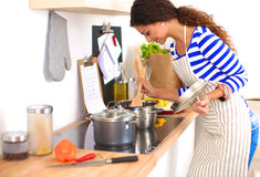 Junge Frau in der Küche, die ein Lebensmittel zubereitet Stockbild