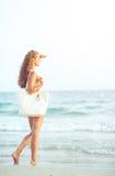 Junge Frau an der Küste, die Abstand untersucht Lizenzfreie Stockfotografie