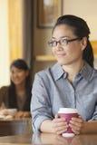 Junge Frau an der Kaffeestube, die weg in der Betrachtung schaut lizenzfreies stockbild