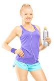 Junge Frau in der laufenden Ausstattung, die mit einer Getränkflasche aufwirft Stockbilder