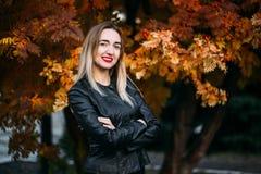 Junge Frau in der Lederjacke auf Herbsthintergrund stockfotografie